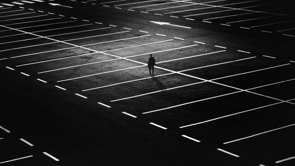 dark night parking lot man alone contrast spooky