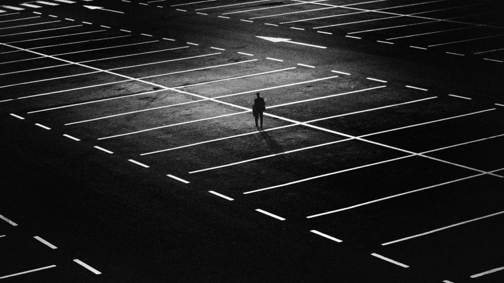dark night parking lot man alone contrast spooky