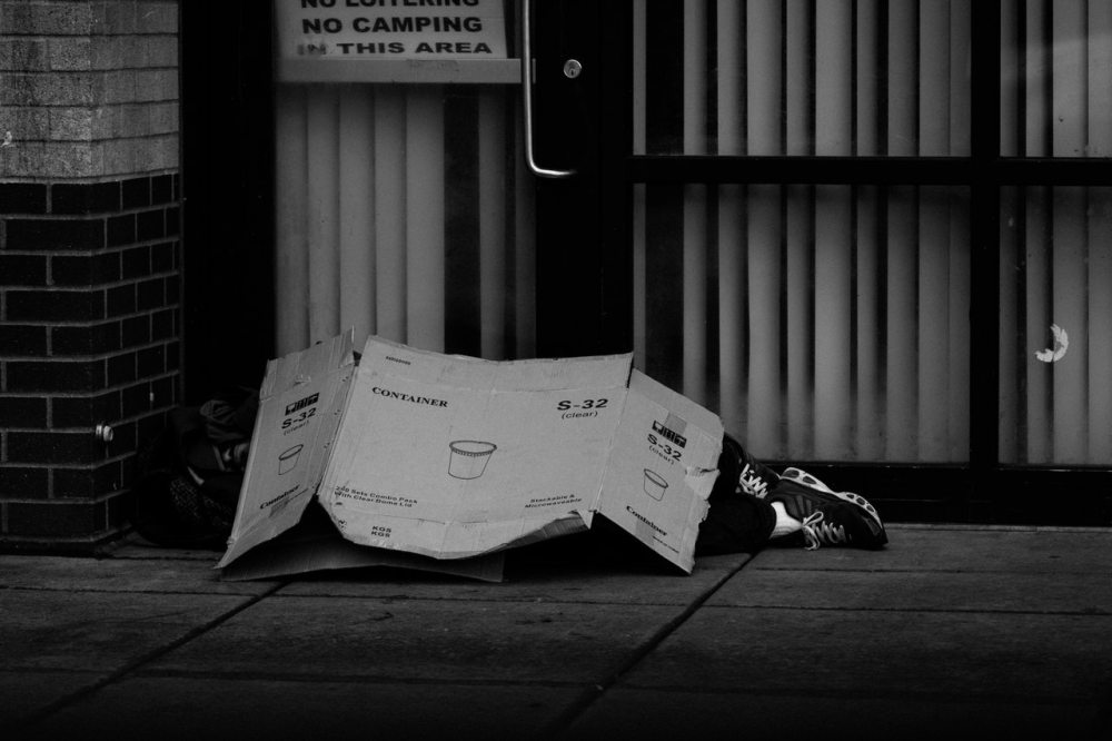 homeless person sleeping cardboard box doorway no camping broken rules destitute